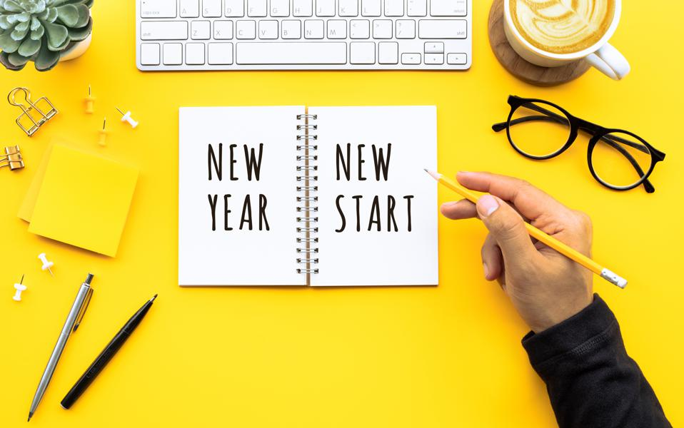New year new start text with youngman writing on notepad on color desk table.Business goal-plan-action and resolution concepts