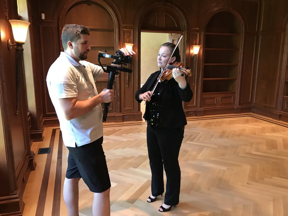 A camera operator videos a woman playing violin in a wood-paneled room.