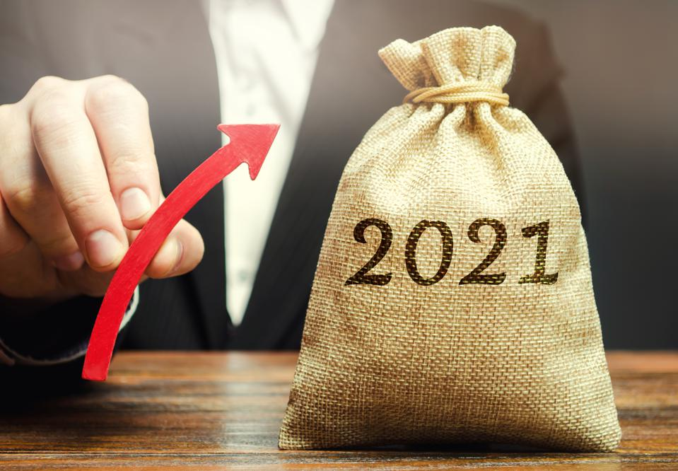 Businessman holds an up arrow near the 2021 money bag. Strategy and budget planning. Vision. Business forecasting. Growth and development of business and economic. Goals and plans. Investment.