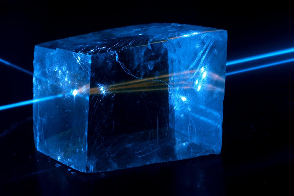 Here, a calcite crystal is struck with a laser operating at 445 nanometers, fluorescing.