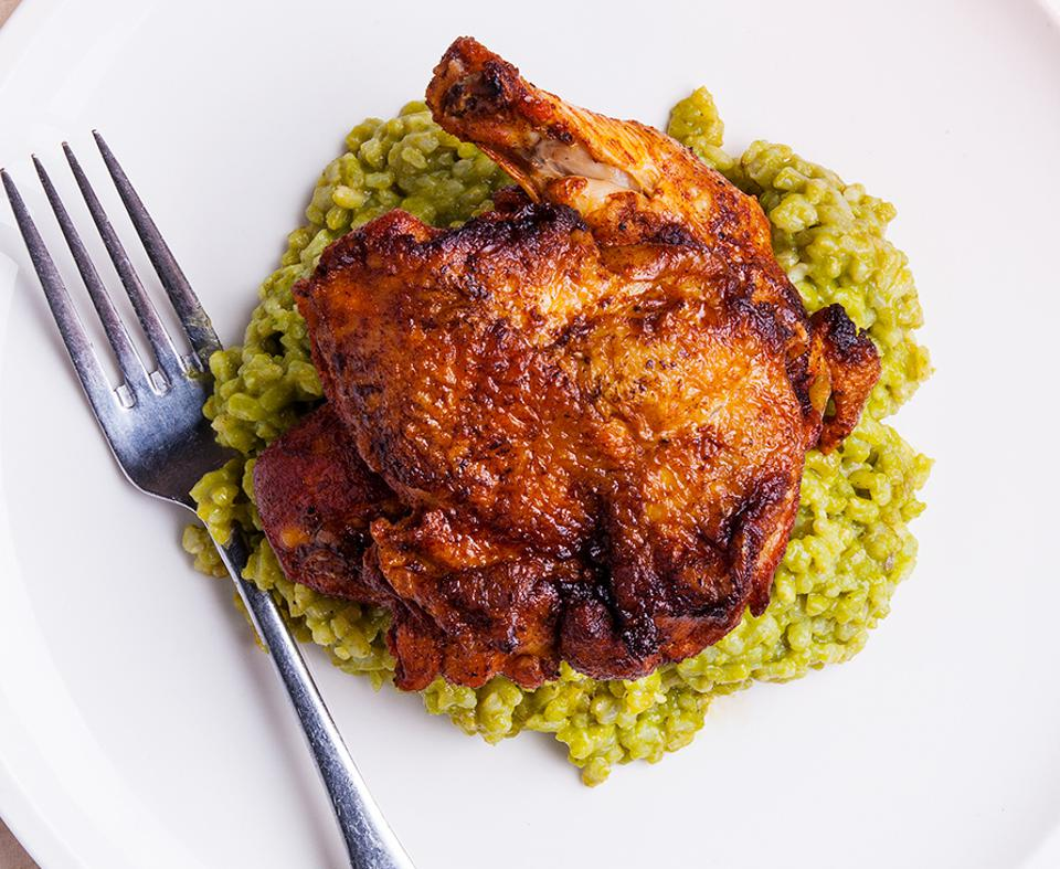 A perfectly roasted chicken on a bed of flavored rice