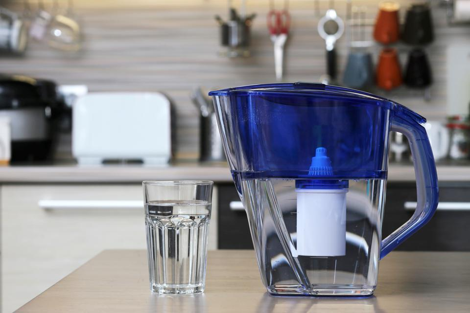 Glass of clean water and filter for cleaning drinking water on the table in the kitchen. Purification of drinking water at home