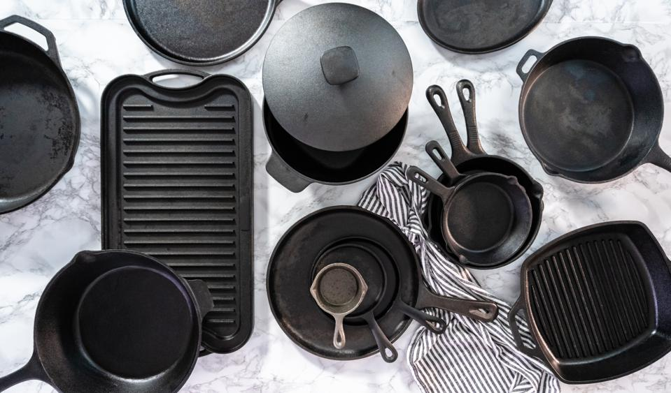 Variety of cast iron frying pans on a marble background.