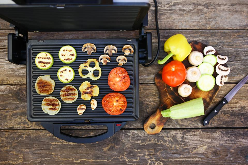 Grilled sausage and vegetables on the electric grill. Top view. Flat lay.