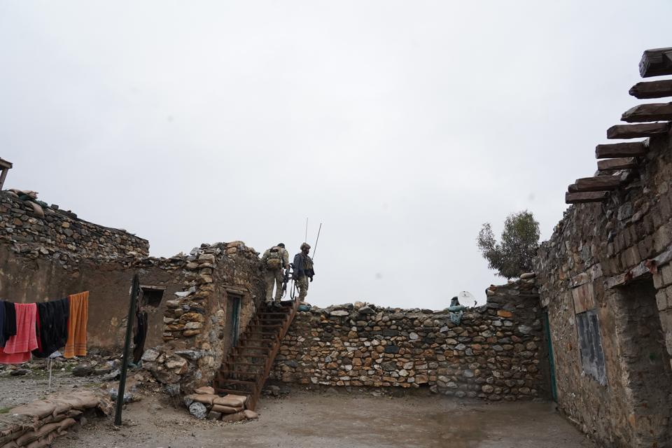 A USAF CCT (with communications antennas at his side) at a mission site in Afghanistan.