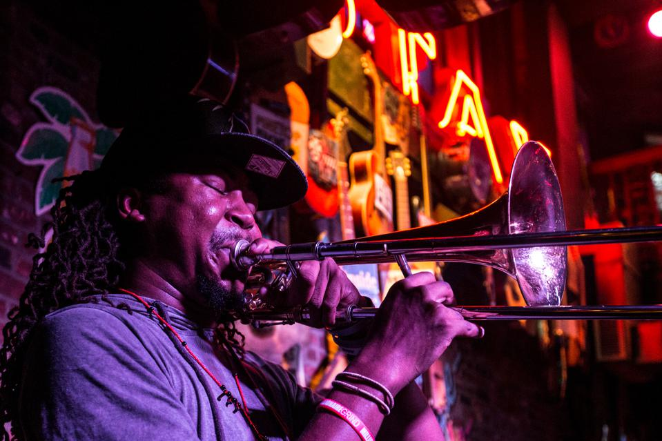 Musician blowing trombone in club setting.