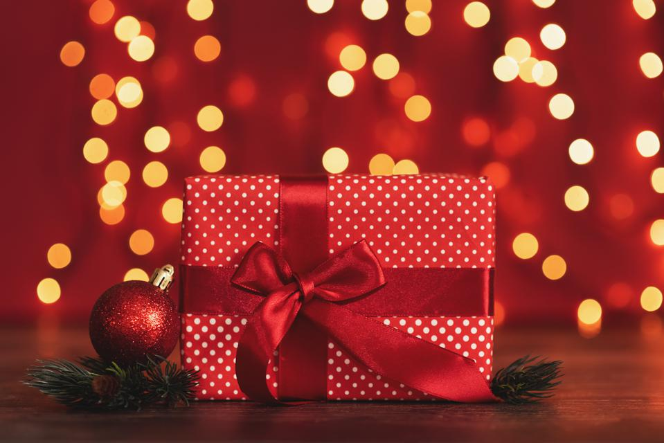 Christmas gifts presents on red background. Simple, classic, red and white wrapped gift boxes with ribbon bows and festive holiday decorations.