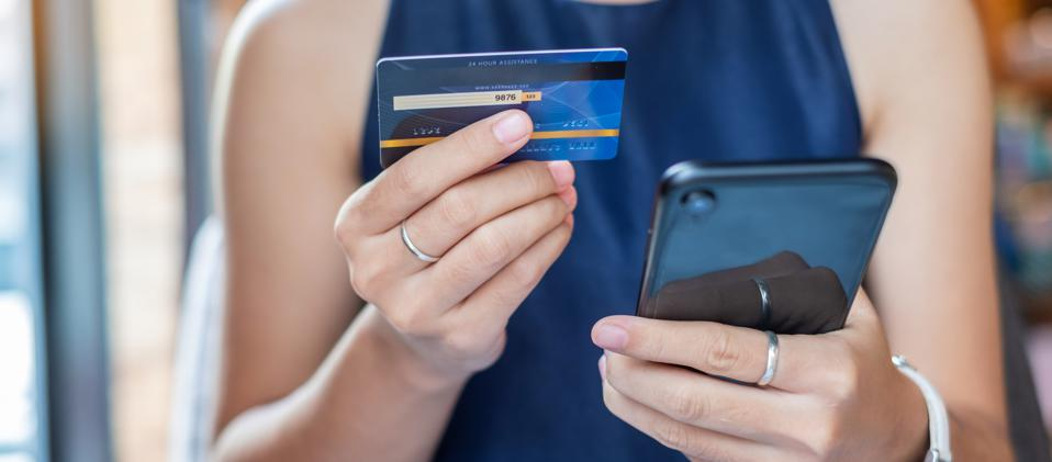Midsection Of Woman Holding Credit Card While Using Mobile Phone For Online Shopping