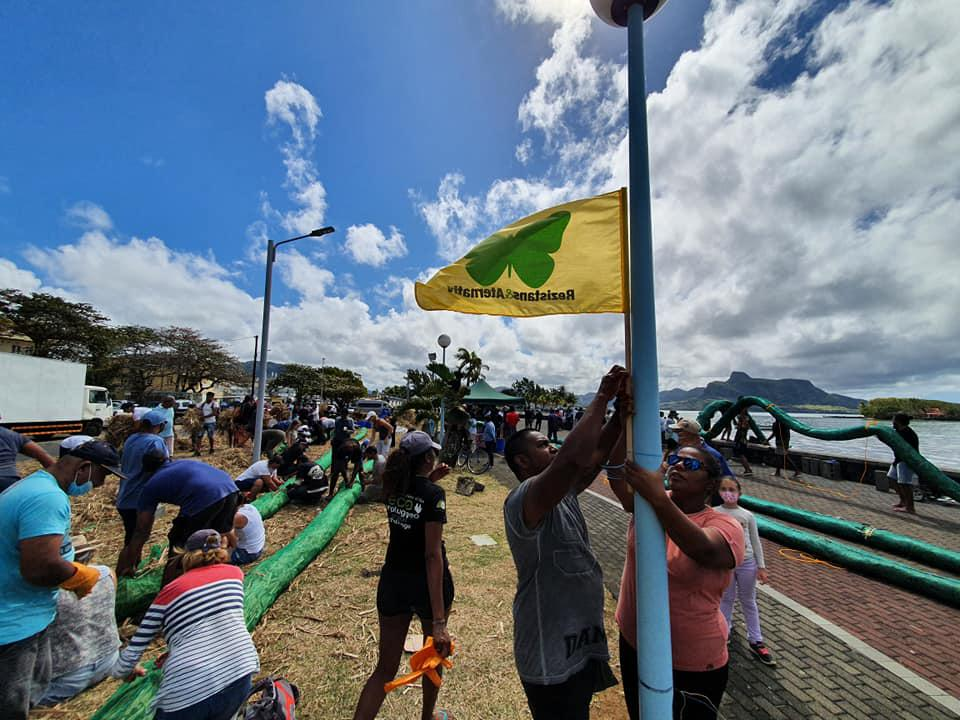 Local community group Rezistans ek Alternativ attach a flag on Mahebourg beach after police tried to prevent the deployment of further oil protection booms