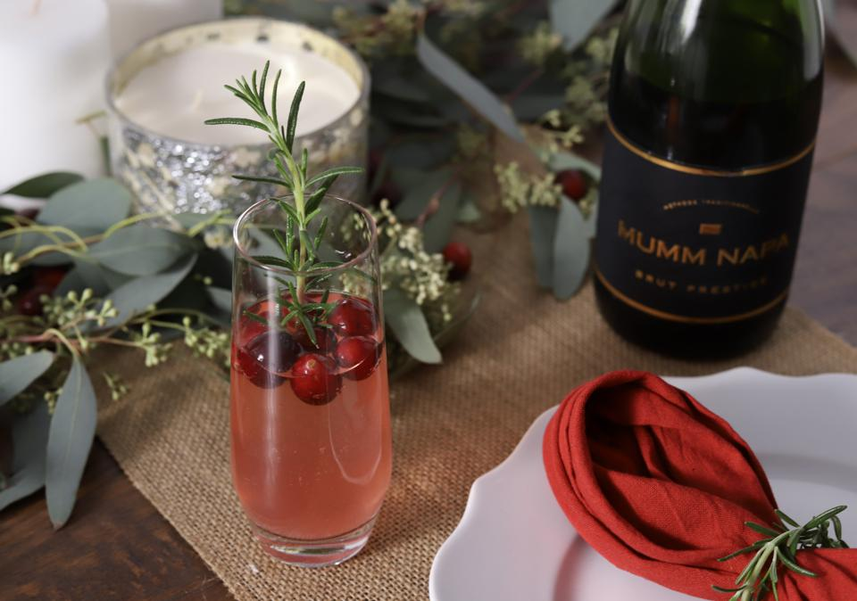 Cranberry cocktail on table with bottle of Mumm Napa Brut reserve