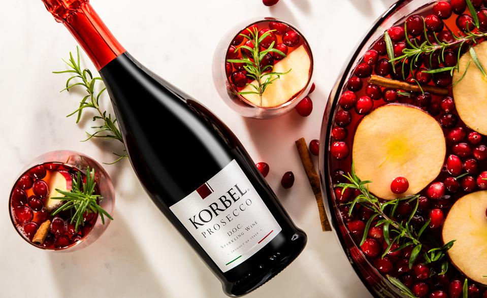 Bottle of Korbel Prosecco with punch bowl and glasses filled with festive cranberry cocktail.