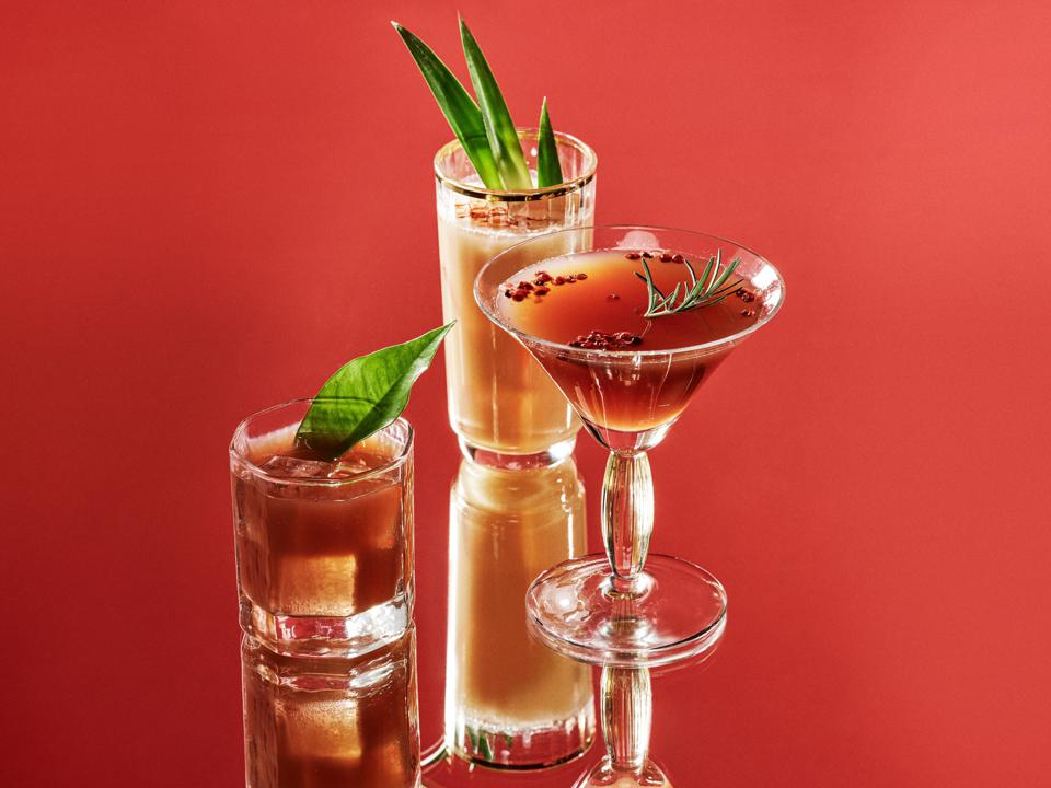 Three cocktail glasses with red and orange liquid are depicted against a red background.