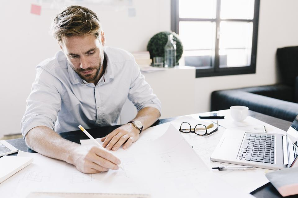 Architect working on construction plan at desk
