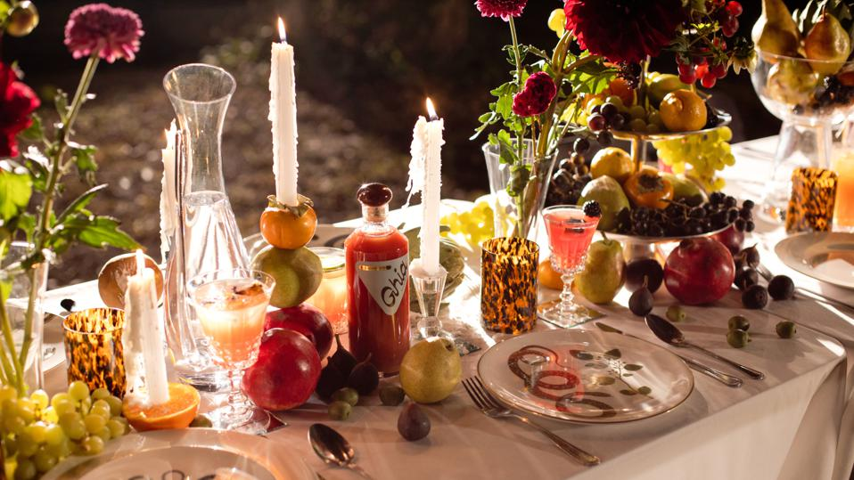 A candlelit dining table is decorated with flowers and fruit.