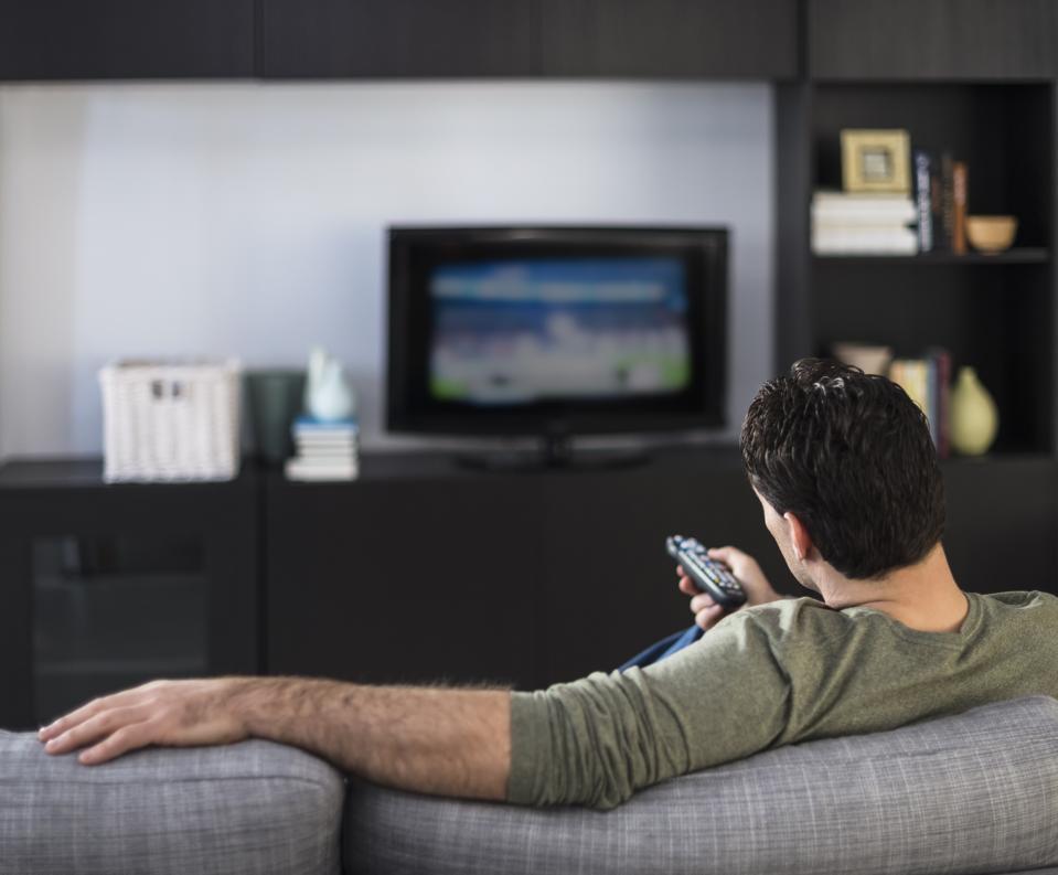 Rear view of man watching tv, Jersey City, New Jersey, USA