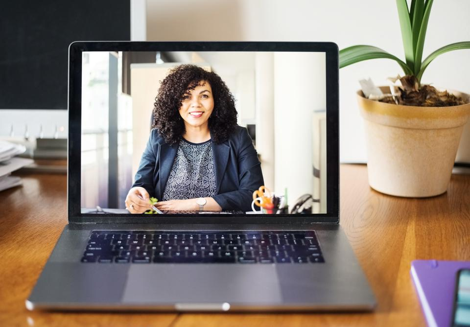 A laptop displays a woman in an office conducting a virtual interview.