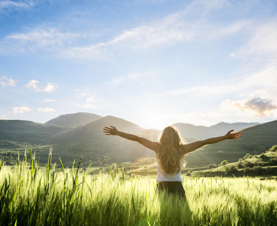 woman in nature with hands outstretched having a fresh morning. 2021 wellness trends