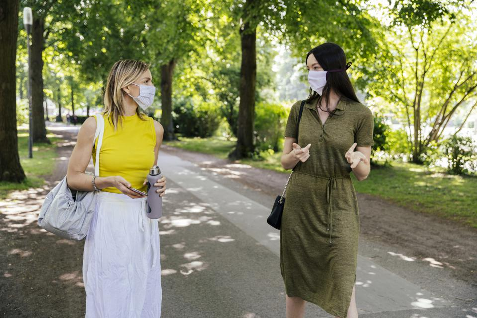 Two women meeting in nature while wearing face masks
