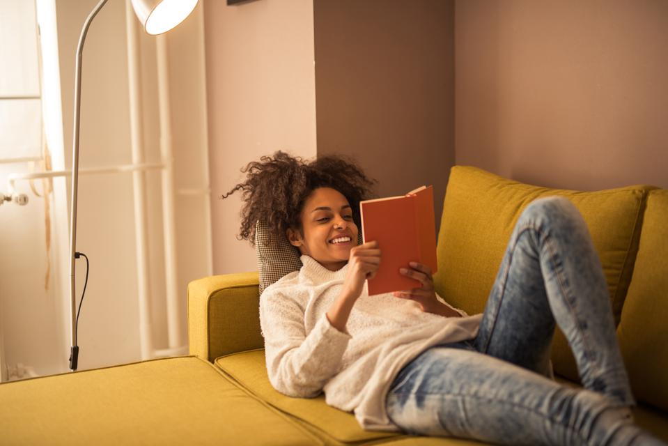 A black woman reads a book on a couch during a digital detox, a 2021 wellness trend