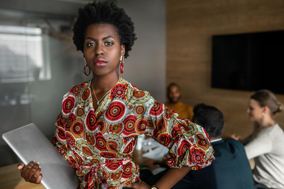 Beautiful young confident professional black african business woman holding laptop, coworkers hold a meeting in background