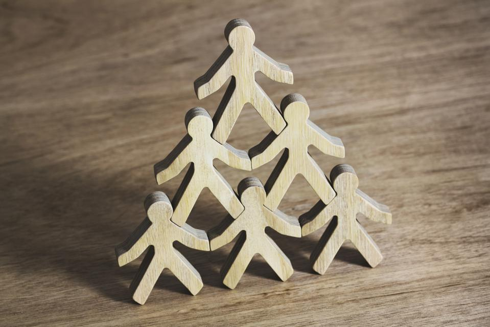 Six wooden model men standing in pyramid formation