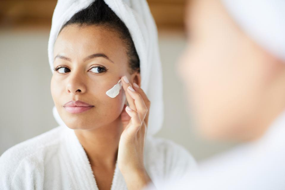 Mixed Race Woman Applying Face Cream. Here's the truth behind 11 skincare myths.