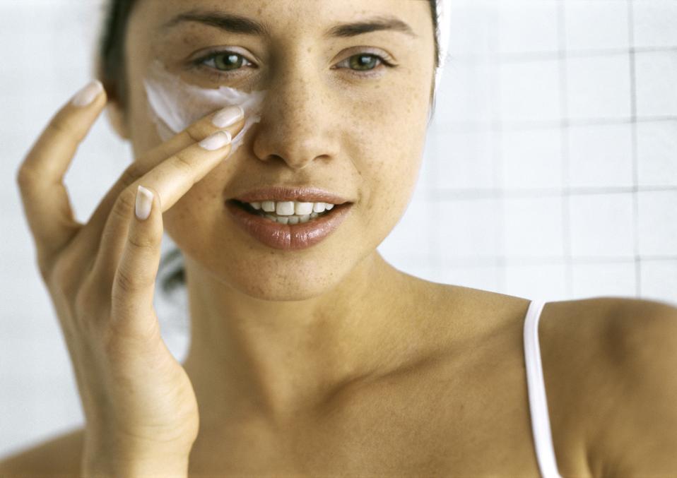 Woman applying moisturizer beneath eye