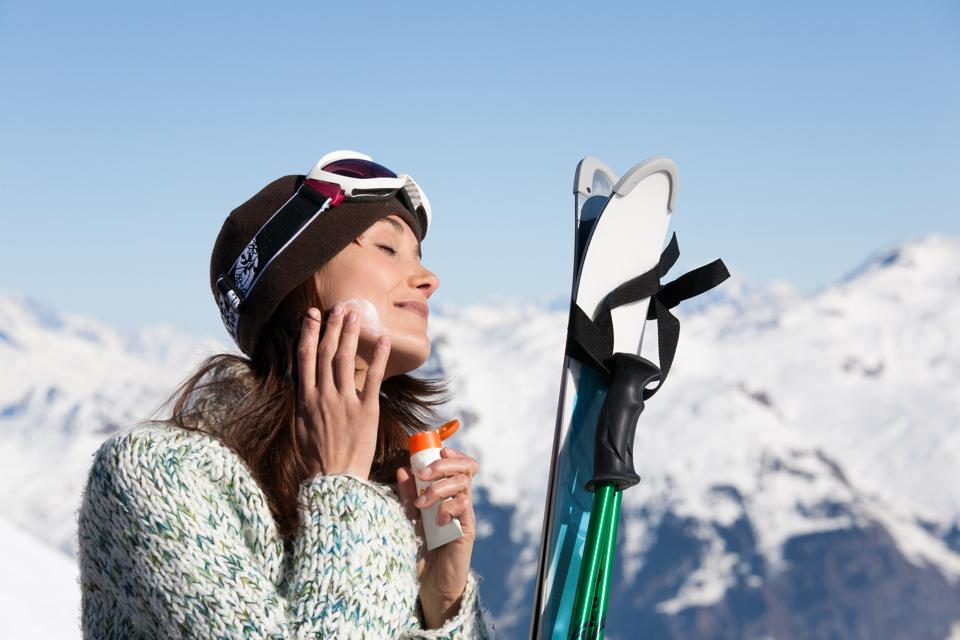 woman in winter applying a sunscreen cream her face while holding skis