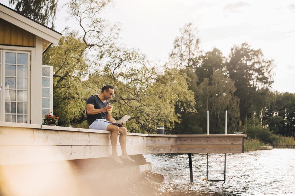 Mature man having juice while using laptop on patio by lake