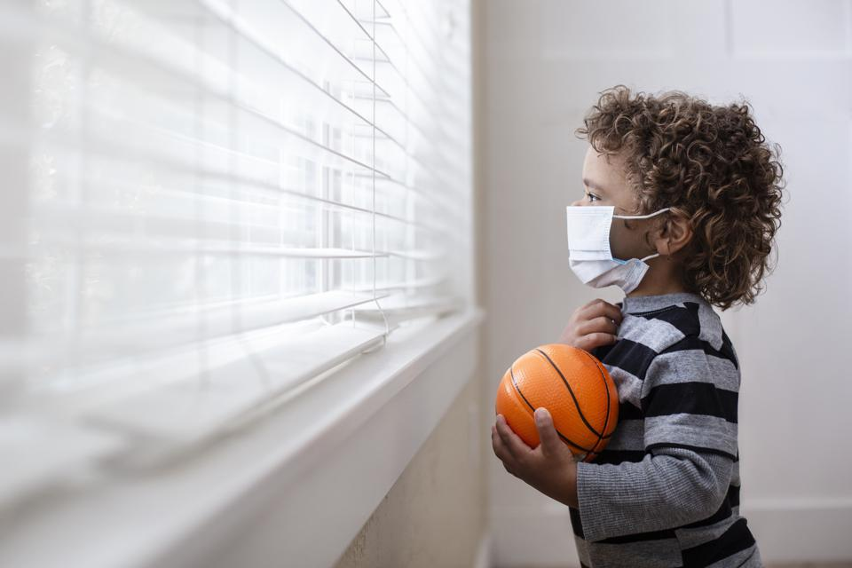 A young boy looking out the window wearing a protective facemark