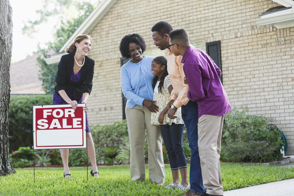 Realtor with black family in front of house for sale