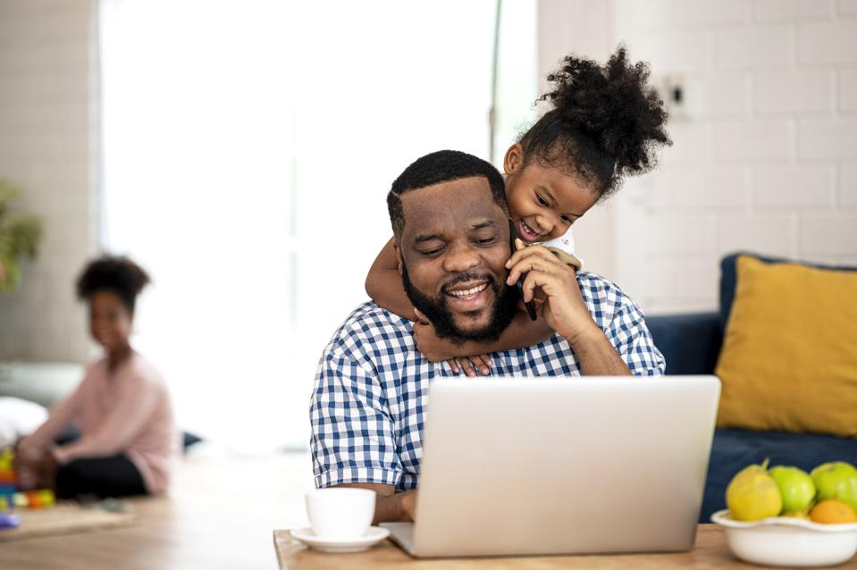 Papa please play with me!. A African Father working from home, talking on call while cute little daughter disturb her father to stop working.