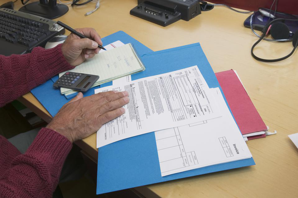 Mature man preparing tax forms, close-up