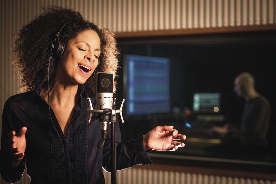 A woman singing into a Sennheiser MK4 microphone in a studio setting