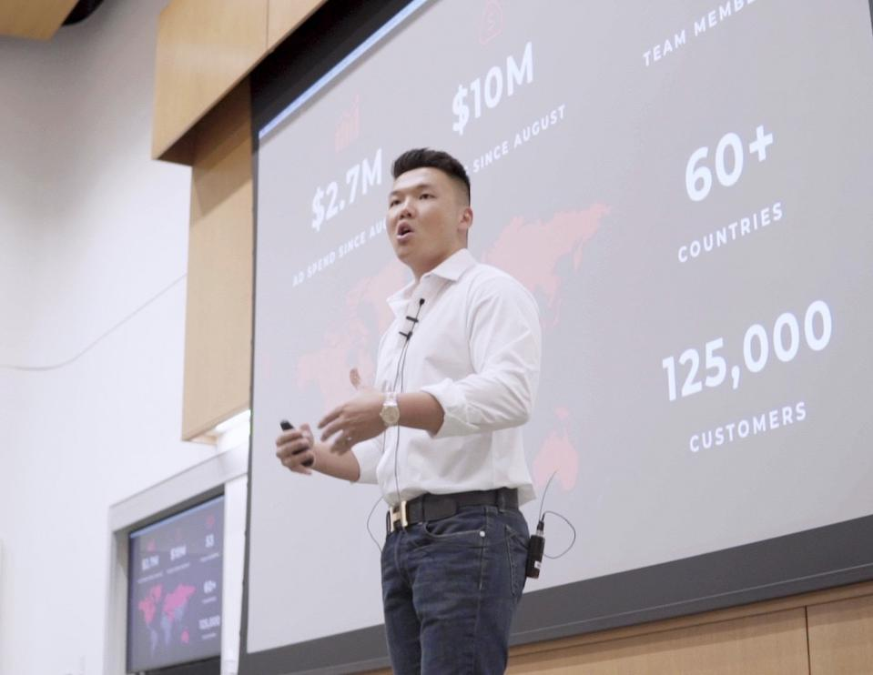 Asian male speaker standing in front of a projector screen giving talk