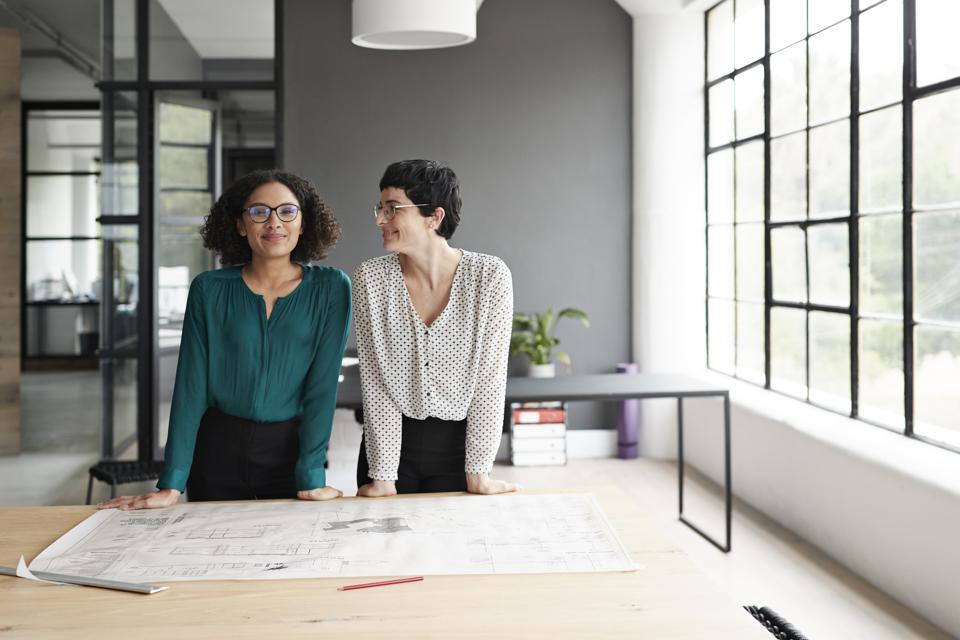 Businesswoman with coworker standing in office