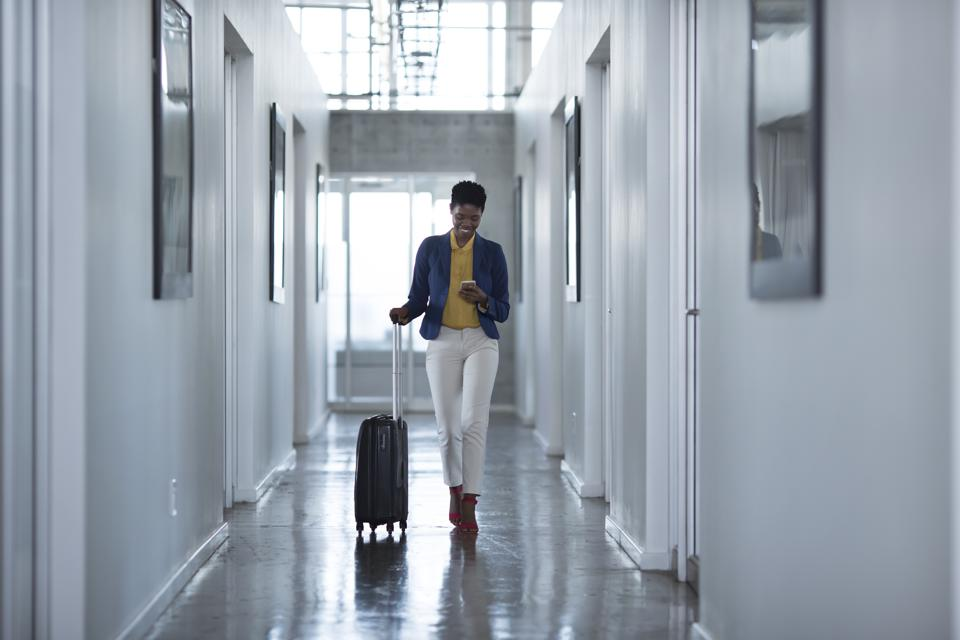 Businesswoman walking down hall way with rolling suitcase