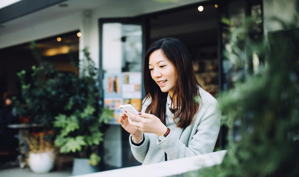 Beautiful Asian lady using smartphone and relaxing in outdoor cafe
