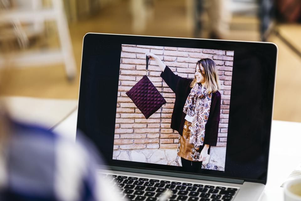 Photo of woman holding bag on laptop screen