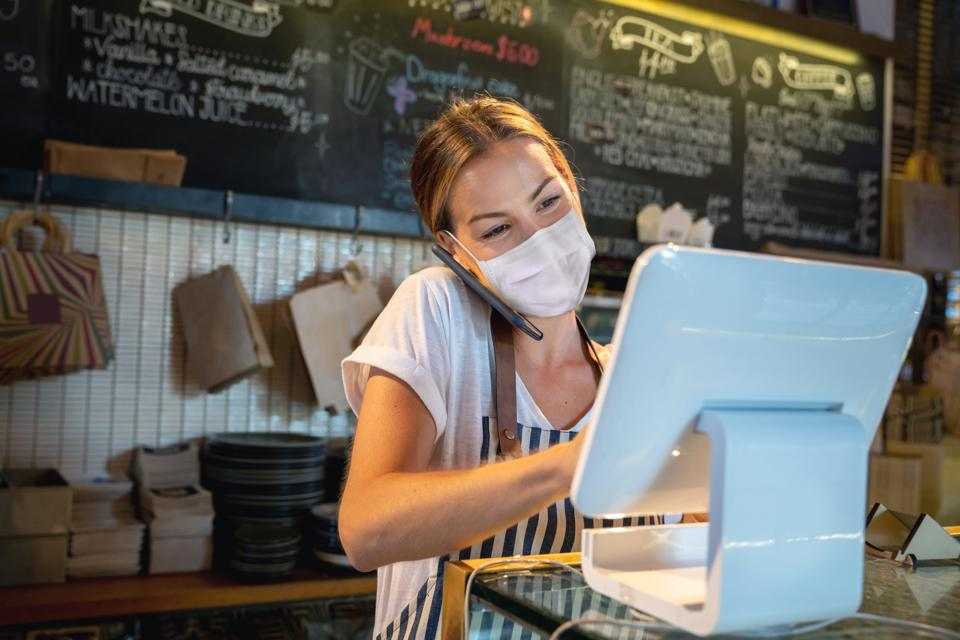 Waitress at a restaurant getting a delivery order on the phone and wearing a facemask