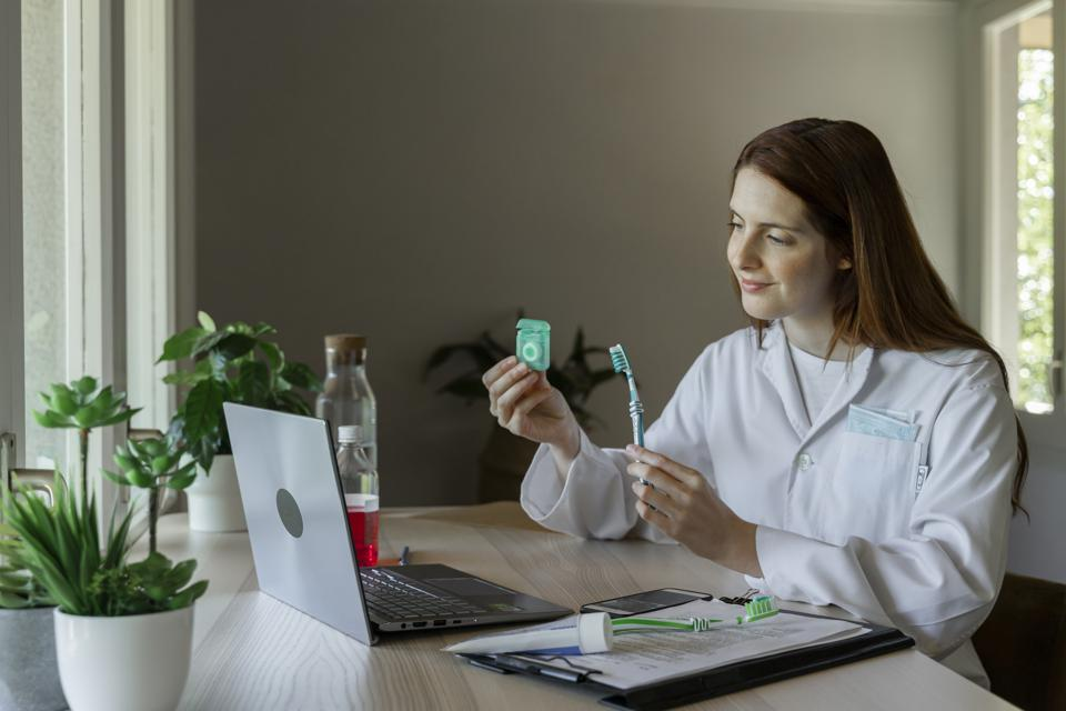 Smiling female dentist showing dental floss and toothbrush to patient through video call