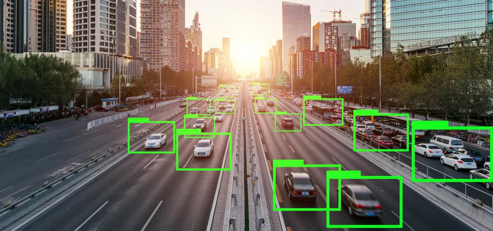 green boxes surround individual self-driving cars on highway in urban setting.