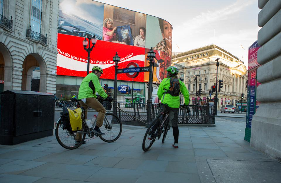 Two cyclists rest in a deserted Piccadilly Circus in London on Christmas day, 2020.