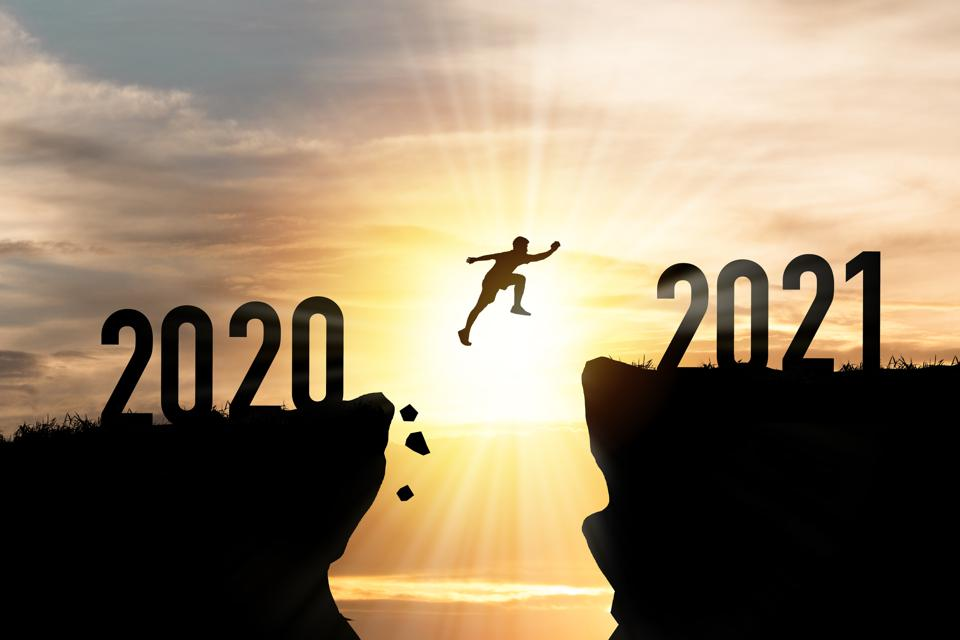 Person jumping from 2020 cliff to 2021 cliff with cloud sky and sunlight.