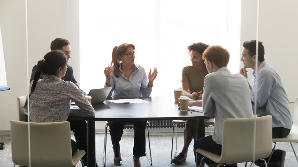 Middle-aged businesswoman speaking at diverse group negotiations at conference table