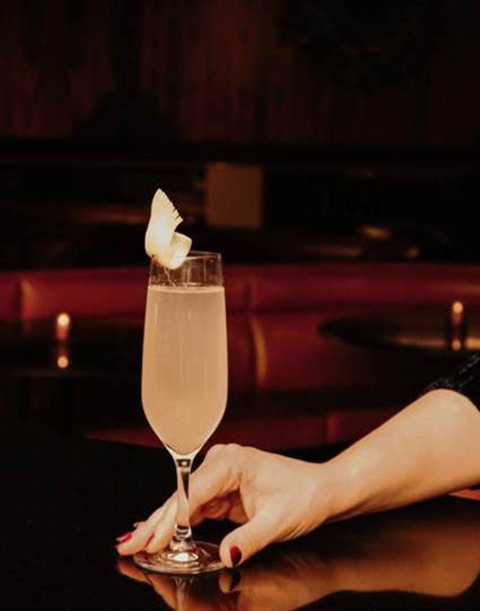 woman's hand with a french 75 cocktail