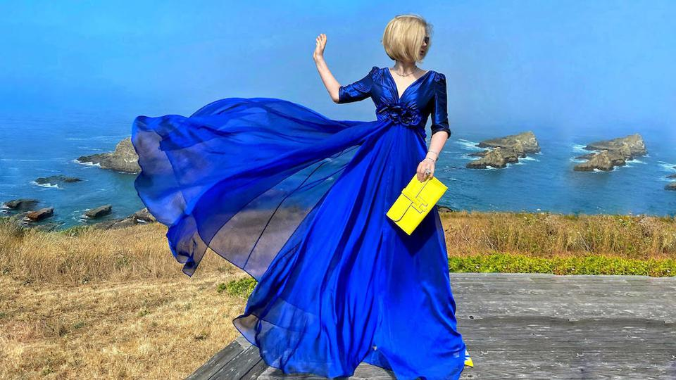 Blonde woman wearing a blue dress holding a yellow handbag in a fashion influencer photo