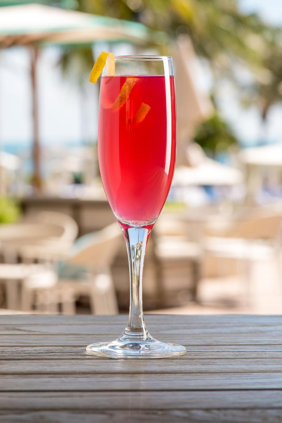 Champagne cocktail with beach backdrop.