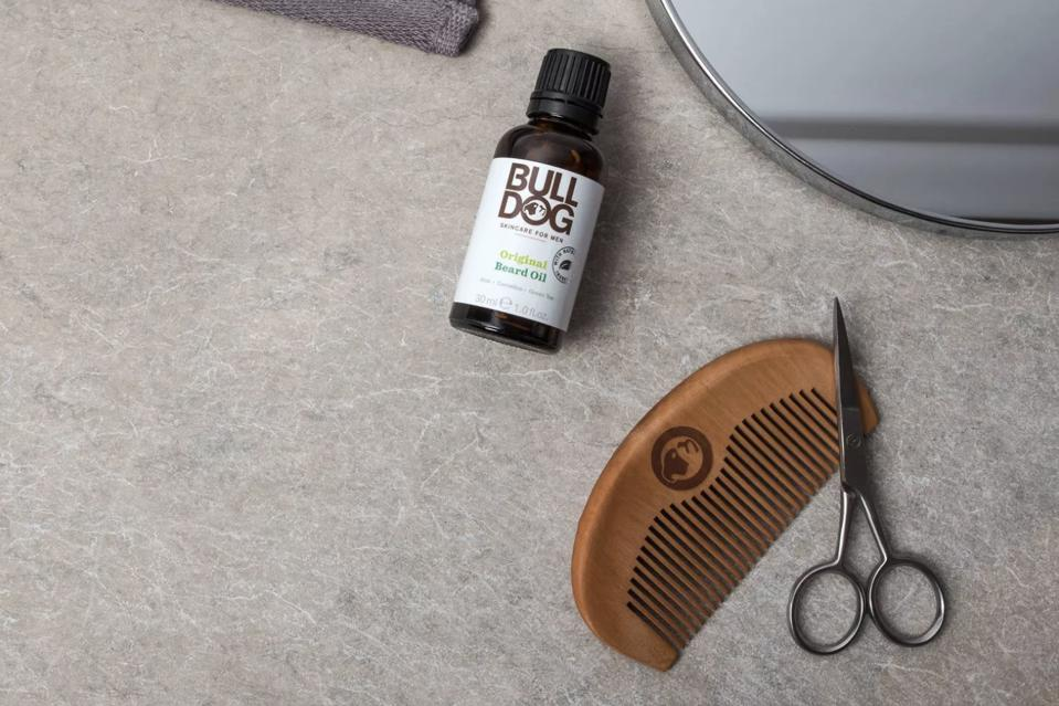 Bulldog beard oil set up on a sink with a beard comb and scissors