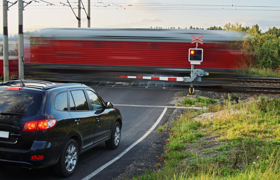 Red train passing through a railway crossing